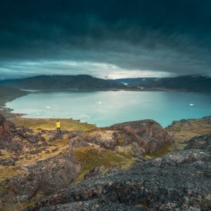 A-lone-traveller-stands-in-Qassiarsuk-and-looks-over-Tunulliarfik-Fjord-toward-Narsarsuaq-by-Stacy-William-Head